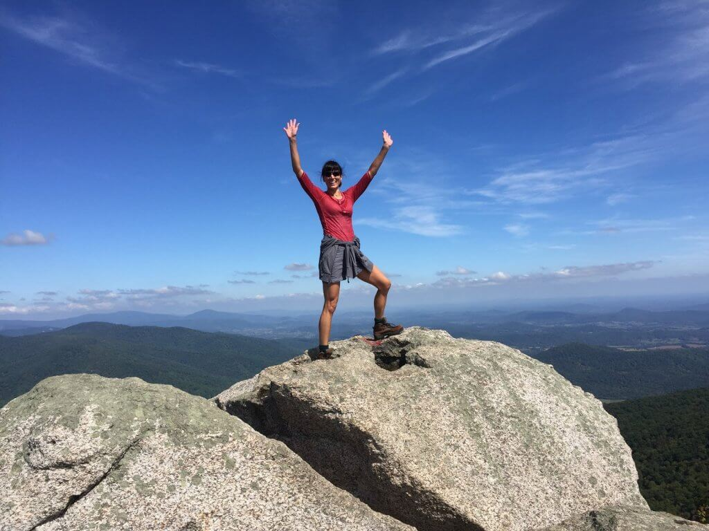 Kat hiking to top of rock - How a Busy Mom Found Financial Freedom Through Real Estate Investing
